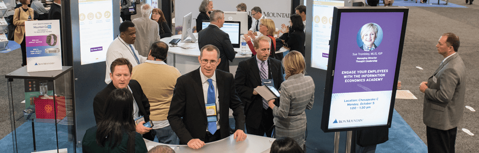 Image of business people at a trade show desk talking to customers