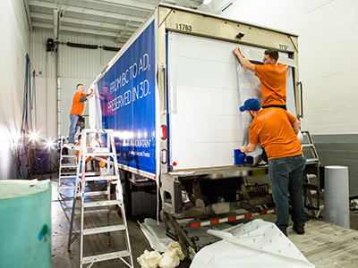 Three workers applying new design to an Iron Mountain truck