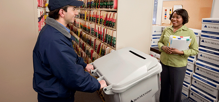Iron Mountain employee wheeling shred bin up to woman holding documents