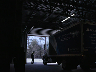 An Iron Mountain employee standing in front of a truck in the garage