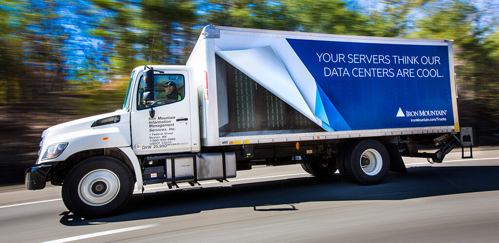 A redesigned Iron Mountain truck driving on the road with its design showing data servers
