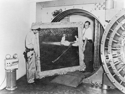 two men moving a painting into a vault