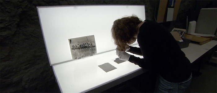 A woman examining a document on a lighted bench
