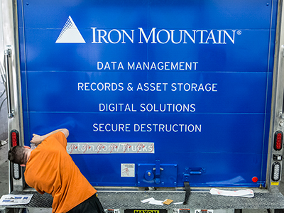 A worker removing a stencil from the back of a newly designed Iron Mountain truck