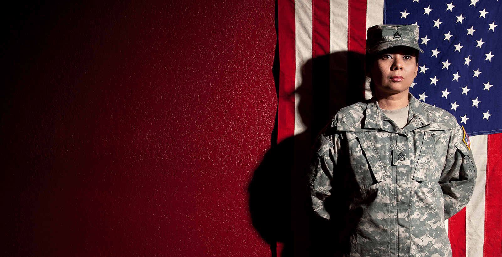 veteran standing in front of american flag