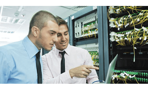 two men looking at information next to server