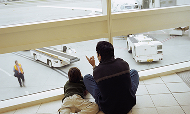 man and child sitting on ground pointing outside an airport window