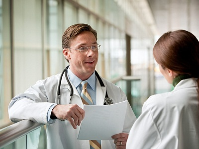 doctor holding paper talking to other doctor