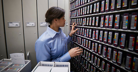 Big Data Basics: Empower Your Enterprise - Employee Looking at Tapes in Vault