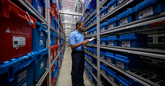 Evaluating a hybrid approach to offsite data storage - Employee with Tape Containers on Shelf
