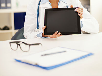 doctor holding up ipad with glasses and notepad on table