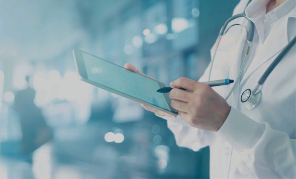 Transitioning to Value-Based Healthcare: The Data Strategies You Should Adopt Now - Doctor Holding Tab | Iron Mountain