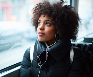woman riding vehicle listening to music with headphones looking out window