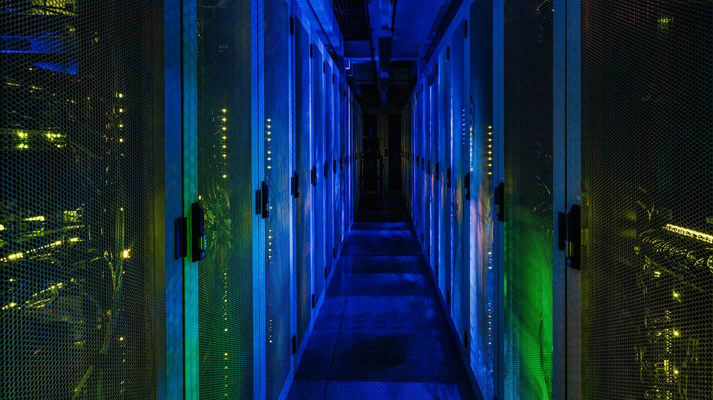 3 months free colocation offer - banner image showing data center cabinets illuminated with blue and green lights