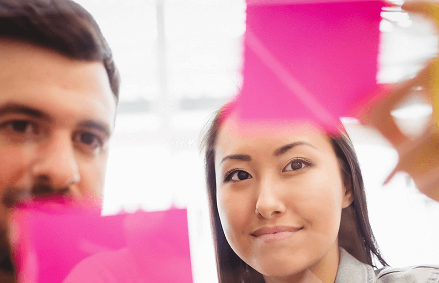 man and woman looking at pink post it note