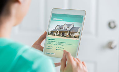 Navigating the Digital Mortgage Revolution - A woman using her phone to search a new house