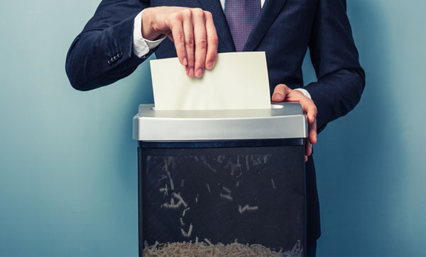 Secure Shredding Why shredding is important to your organization -man doing shreddign | Iron Mountain