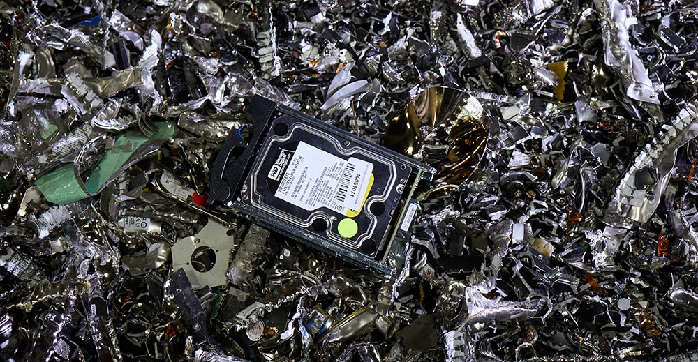hard drive sitting on pile of trashed computer parts