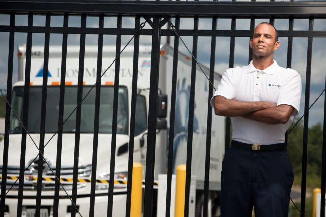 iron-mountain-employee-standing-infront-of-gate-with-truck-in-background