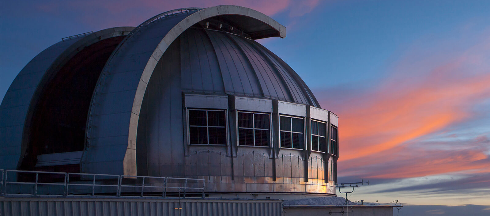 A photo of a giant telescope with a sunset in the background.
