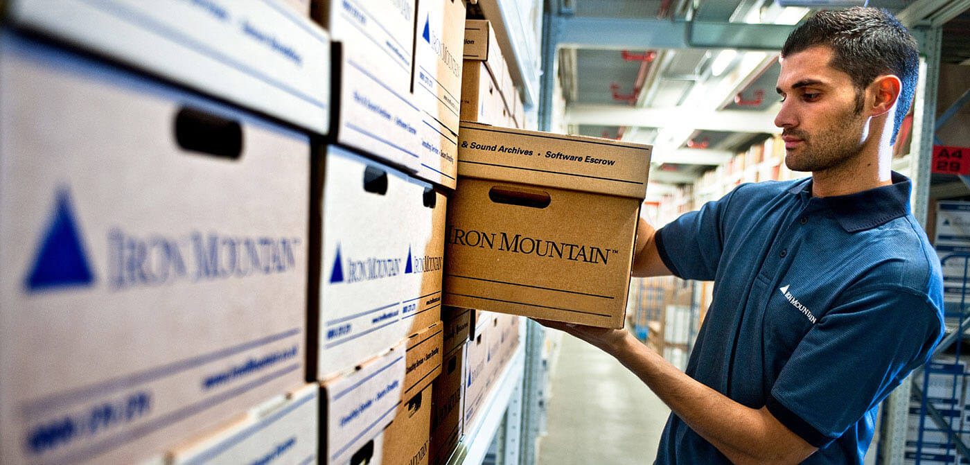 Iron Mountain Employee pulling box off shelf