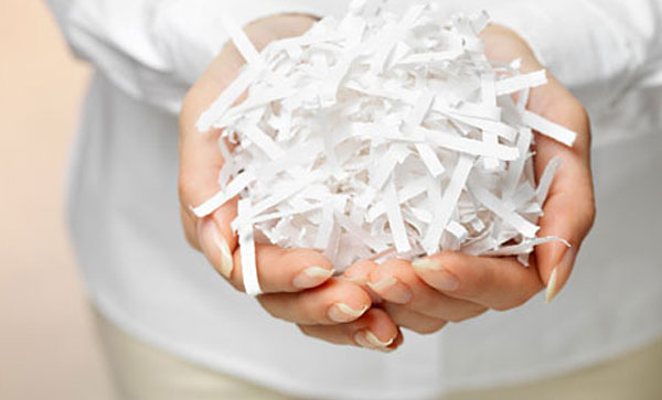 Secure Shredding- A person holding shredded paper