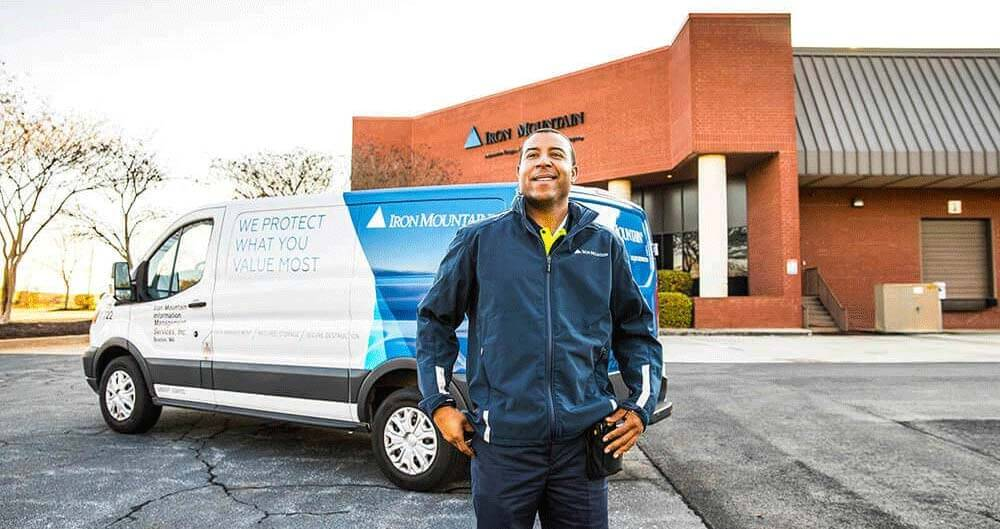 iron mountain employee standing in front of truck and facility smiling