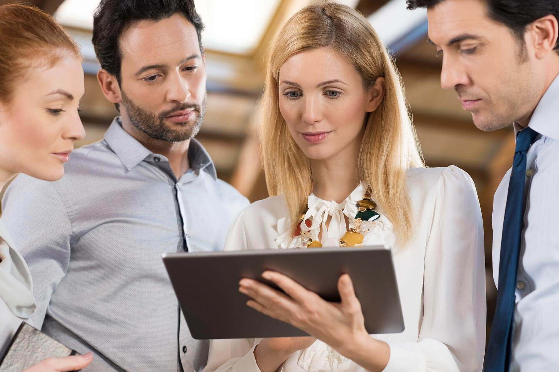 workflow automation highlight two people standing around woman holding tablet