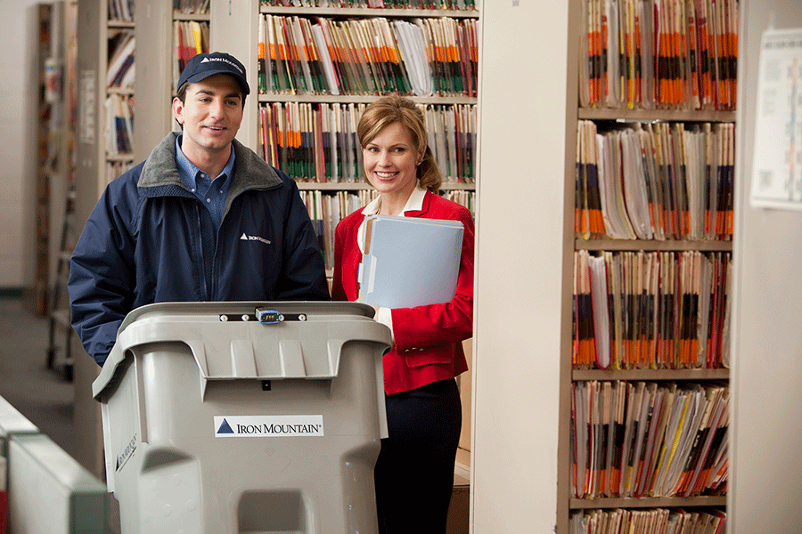 Iron Mountain employee wheeling shred bin out of business with woman smiling