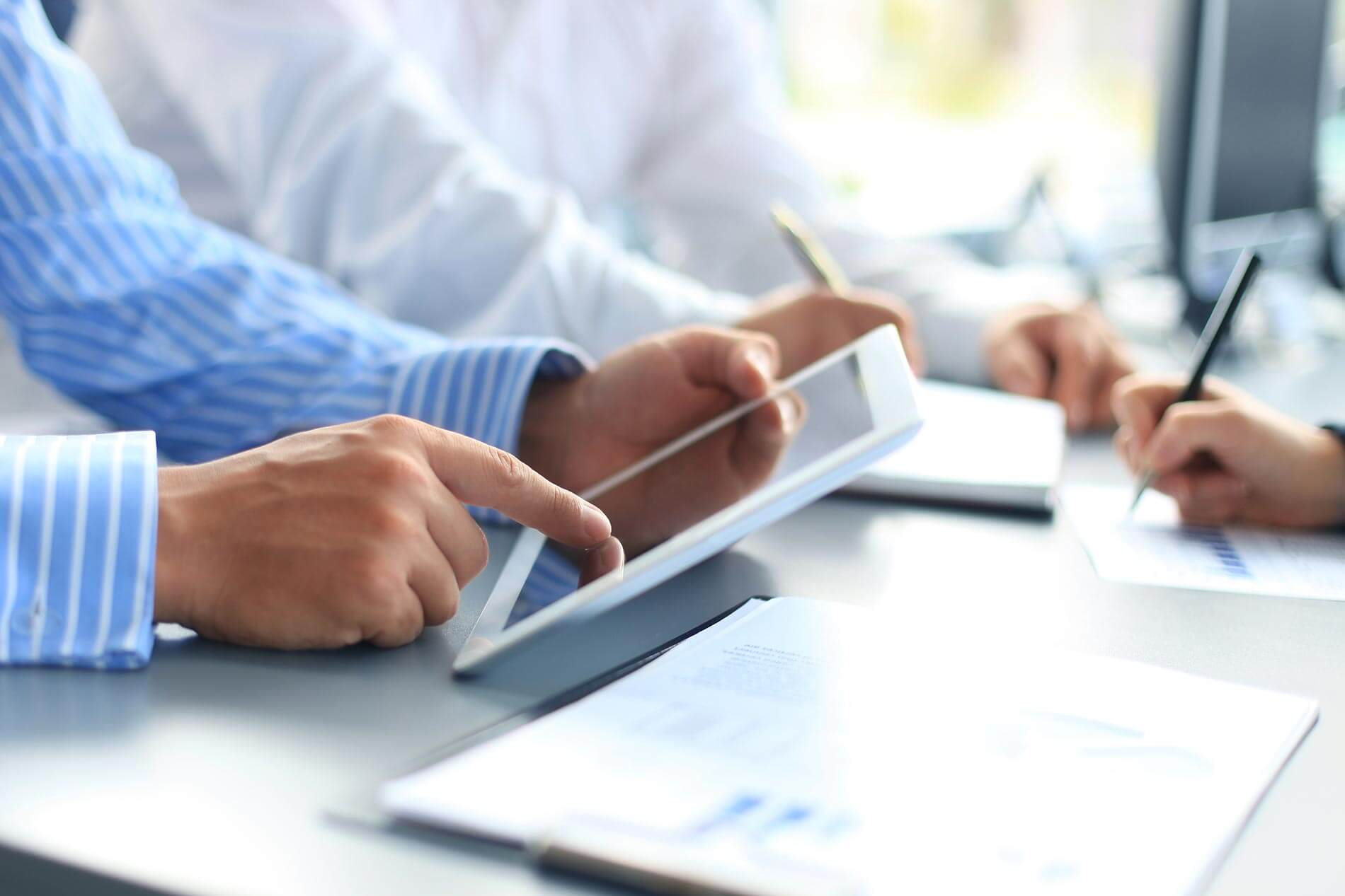 workflow automation accounts payable banner - people working on tablet and documents at table