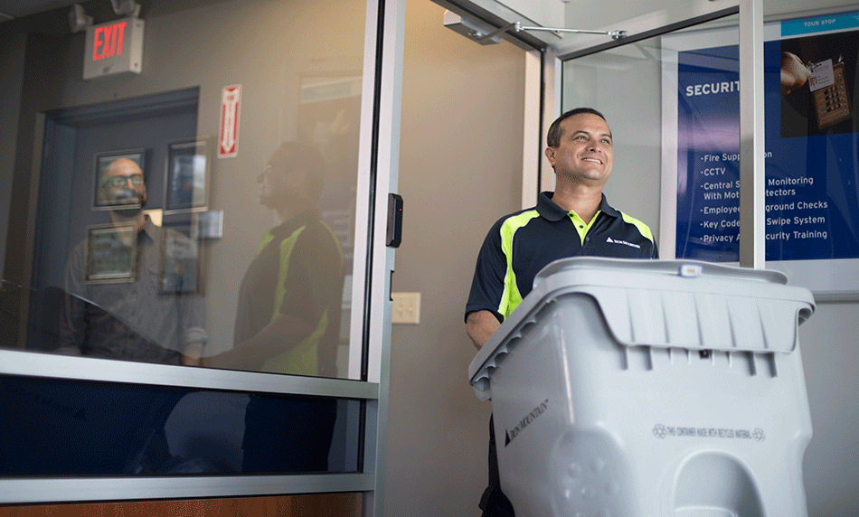 secure-destruction-banner-iron-mountain-employee-wheeling-shredding-container