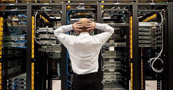 Information Overload Leads to Security Oversights - Man in front of server